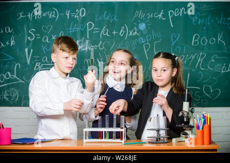 Fascinating chemistry. Group school pupils study chemistry in school. Boy and girls enjoy chemical experiment. Organic chemistry is study of compounds containing carbon. Basic chemical reactions. - Stock Photo