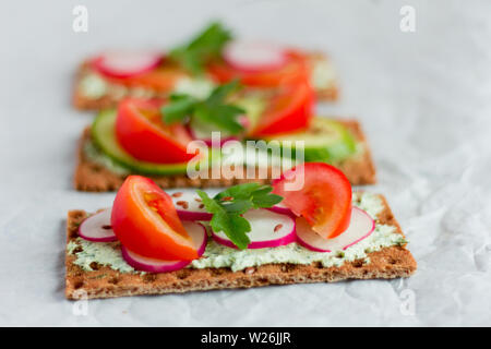 Delicious diet sandwiches with cottage cheese with herbs and vegetables on a white background - Stock Photo