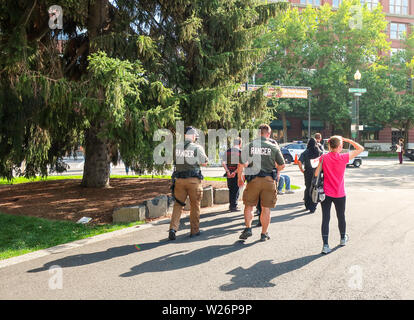 Local police and ranger officers escort a handcuffed suspect through Riverfront Park in the downtown area of Spokane, Washington. - Stock Photo