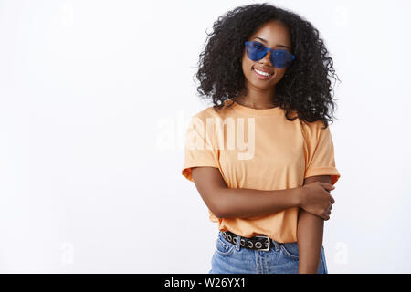 Charming friendly-looking shy dark-skinned female blushing posing friend take photo touching arm insecure tilting head smiling lovely cute, wearing tr - Stock Photo