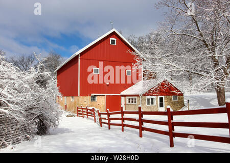 Rural landscape with red barn, wooden red fence and trees covered by fresh snow in sunlight. Scenic winter view at Wisconsin, Midwest USA, Madison are - Stock Photo