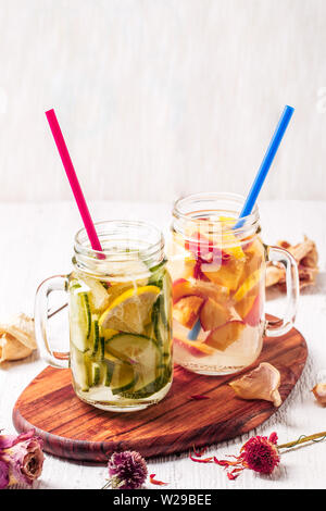Two mugs of infused detox diet refreshing waters - first with cucumber and lemon, second with lemon and peach - Stock Photo