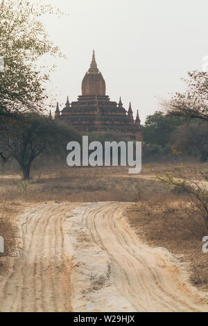 Empty dirt road leading towards pagodas of ancient Bagan temple complex during sunrise golden hour in Myanmar. - Stock Photo