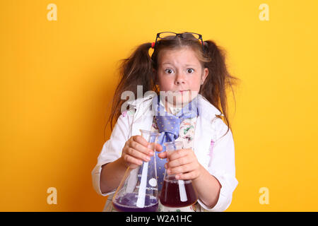 MR - Science Geek Young Girl / Female - Age 7 - looking crazy at camera holding borosilicate science beakers full of chemicals on yellow background - Stock Photo