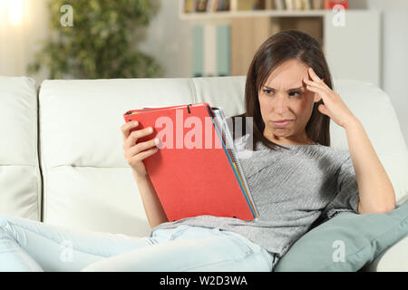 Frustrated student trying to learn sitting on a couch in the living room at home - Stock Photo