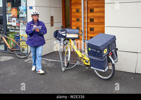 French postwoman and electric delivery bike - Stock Photo