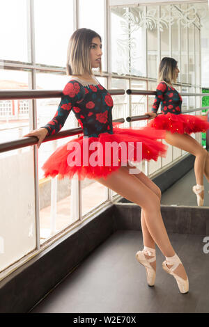 Ballet woman reclining on the dance studio bar while reflecting in the mirror - latina dancer - Stock Photo