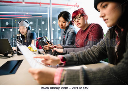 Female compute programmers coding in conference room meeting - Stock Photo