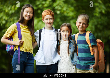 Group of happy interracial friends with satchels standing in park and embracing each other while posing for camera - Stock Photo