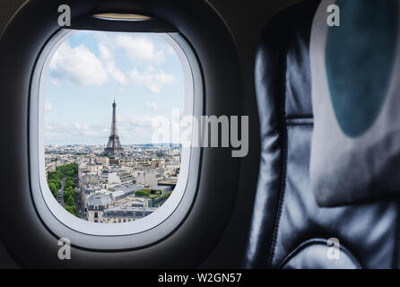 Traveling Paris, France famous landmark and travel destination in Europe. Aerial view Eiffel Tower through airplane window - Stock Photo