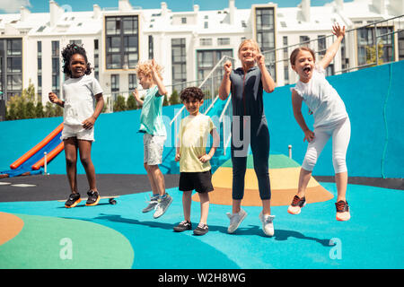Happy children jumping up in the air. - Stock Photo