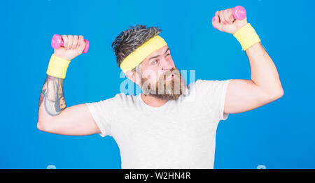 Man bearded athlete exercising dumbbell. Athlete training with tiny dumbbell. Motivated athlete guy. Sportsman training with dumbbells blue background. Improve your muscles. Use weights or dumbbells. - Stock Photo