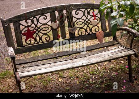 old wooden bench decorated with hearts at the Melaten cemetery, Cologne, Germany.  mit Herzen geschmueckte alte Holzbank auf dem Melatenfriedhof, Koel - Stock Photo