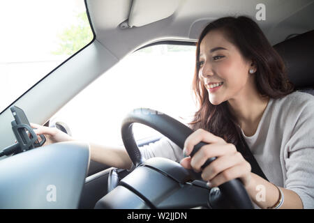 Asian woman using phone and sending a message behind the wheel, Female driving a car with using navigation or application on smartphone, Smart technol - Stock Photo