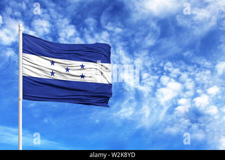National flag of Honduras on a flagpole in front of blue sky - Stock Photo