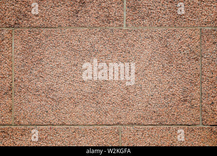 Close-up of part of a bumpy red granite block stone wall with vignette. High resolution full frame background texture. - Stock Photo