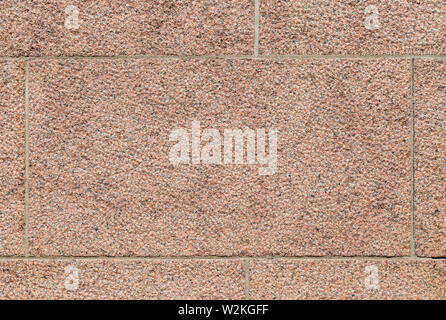 Close-up of part of a bumpy red granite block stone wall. High resolution full frame background texture. - Stock Photo