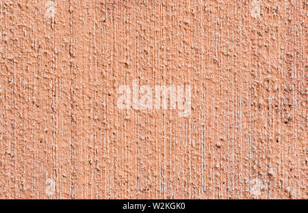 Macro close-up of plastered, painted, faded, rough and red, orange or peachy concrete or stone wall. High resolution full frame textured background. - Stock Photo