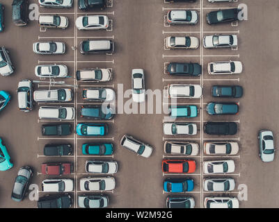 A view from a height to the parking lot. The process of parking. Searching for space in a busy car park. Parking maneuvers. Park lot lane markings - Stock Photo