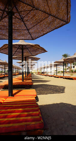 sandy beaches with umbrella and sunbeds in Egypt - Stock Photo