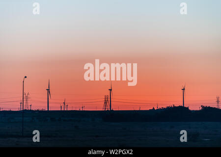 Snyder, USA view of wind turbine farm and power lines in Texas countryside industrial town and horizon with colorful red sunset - Stock Photo