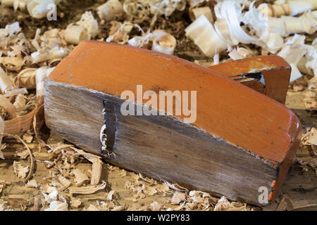 An orange coloured wooden block plane and wood shavings at the heritage Britannia Ship Yard in Steveston British Columbia Canada - Stock Photo