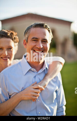 Portrait of happy mature man being hugged by his wife. - Stock Photo