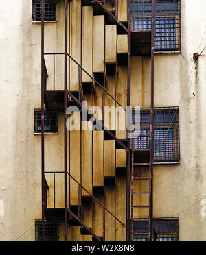 Urban building  back alley fire escape rusty stairs on aged wall. - Stock Photo