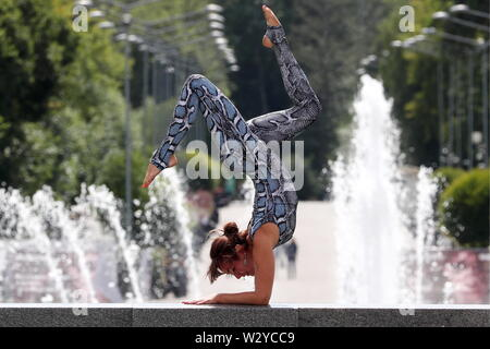 Moscow, Russia. 10th July, 2019. MOSCOW, RUSSIA - JULY 10, 2019: A girl doing yoga in Gorky Park. Anton Novoderezhkin/TASS Credit: ITAR-TASS News Agency/Alamy Live News - Stock Photo