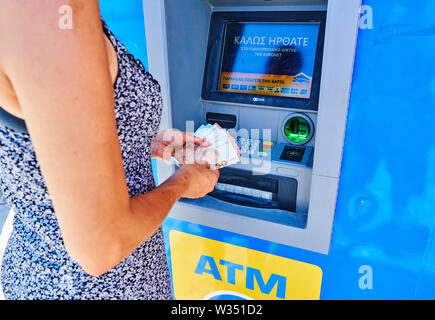 Tourist takes cash from a ATM cash machine in Akrotiri near Oia and Fira, Santorini , Greece at 02.06.2019. © Peter Schatz / Alamy Stock Photos - Stock Photo