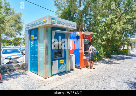 Tourist takes cash at ATM cash machine of Euro Bank at Perissa Beach near airport and Oia and Fira, Santorini , Greece at 06 June.2019. © Peter Schatz - Stock Photo