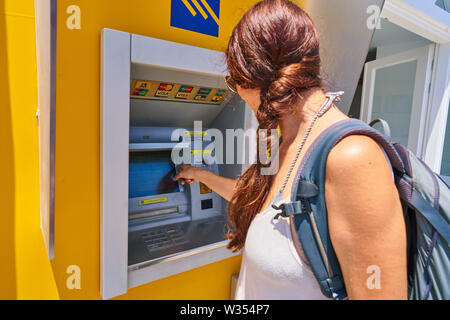 Tourist takes cash at ATM cash machine of Piraeus Bank at Perissa Beach near airport and Oia and Fira, Santorini , Greece at 06 June.2019. © Peter Sch - Stock Photo