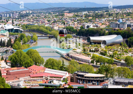 Tbilisi, Georgia - April 29, 2017: Tbilisi red cable car cabins and aerial city skyline panoramic view - Stock Photo