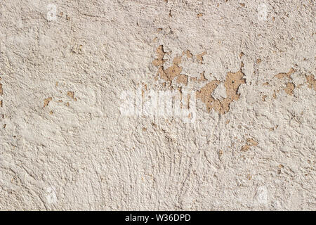 Old cracked weathered shabby beige painted plastered peeled wall background - Stock Photo