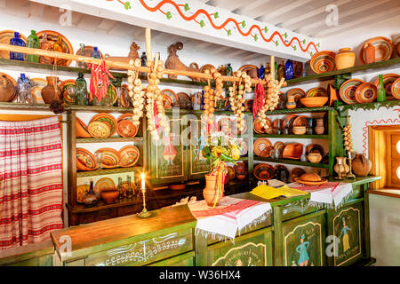 Ceramic painted bowls, plates and jugs on a wooden shelf on the wall, an old counter with glassware in the interior of an old Ukrainian rural cafe and - Stock Photo