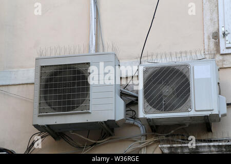 Two air conditioners hang on the wall of the house. - Stock Photo