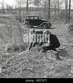 Lifestyle in the 1950s. A young couple having a car drive in the countryside,  has stopped  to pick some flowers on the roadside. They have brought a portable radio recieiver along and listens to it. Sweden 1952.  Kristoffersson Ref BF77-5. - Stock Photo