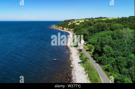 30 June 2019, Denmark, Helligpeder: The west coast of the Danish Baltic Sea island near the small fishing village Helligpeder (aerial photo with a drone). The island Bornholm is, together with the offshore archipelago Ertholmene, Denmark's most eastern island. Thanks to its location, the island of Bornholm counts many hours of sunshine. Photo: Patrick Pleul/dpa-Zentralbild/ZB - Stock Photo
