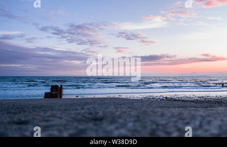 Colorful sunset clouds over sea horizon, view from the seafront through wooden breakwater. Cardigan Bay in Barmouth, North Wales, UK - Stock Photo