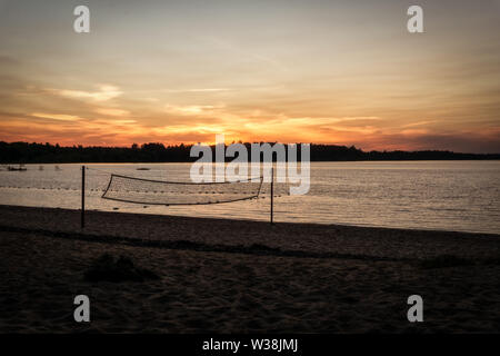 A beautiful sunset at Black Bear Beach, Canada, Petawawa, in the foreground a volleyball net, - Stock Photo