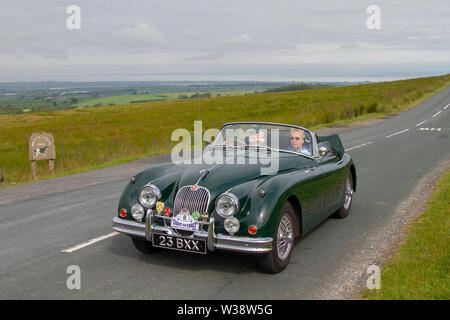 Jaguar XK150 DHC at Scorton, Lancashire. UK Weather 13th July, 2019. Sunny conditions as the Lancashire Car Club Rally Coast to Coast crosses the Trough of Bowland. 74 vintage, classic, collectible, heritage, historics vehicles left Morecambe heading for a cross county journey over the Lancashire landscape to Whitby. A 170 mile trek over undulating landscape as part of the classics on tour car club annual event. Credit: MediaWorldImages/Alamy Live News - Stock Photo