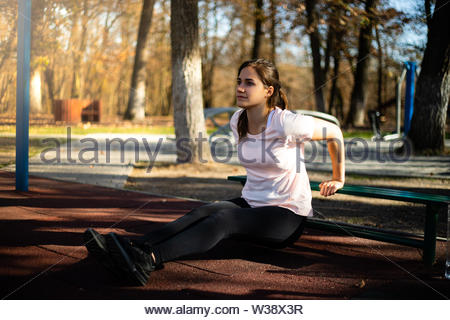 Beautiful woman doing sport on outdoor park during fall and sunset - triceps exercise - Stock Photo