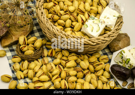 Pistachio and nougat in a wicker basket near a white plate with dates and nougat among the stones and dry twigs are on blue checkered paper - Stock Photo