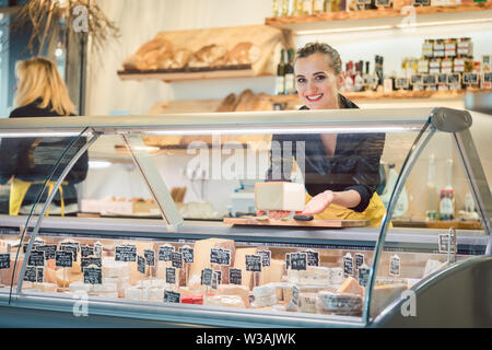 Young Sales lady at the cheese counter in a supermarket - Stock Photo