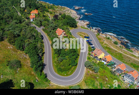07 July 2019, Denmark, Gudhjem: A serpentine road in Gudhjem, a small town on the north coast of the Danish Baltic Sea island Bornholm (aerial view with a drone). The island Bornholm is, together with the offshore archipelago Ertholmene, Denmark's most eastern island. Thanks to its location, the island of Bornholm counts many hours of sunshine. Photo: Patrick Pleul/dpa-Zentralbild/ZB - Stock Photo