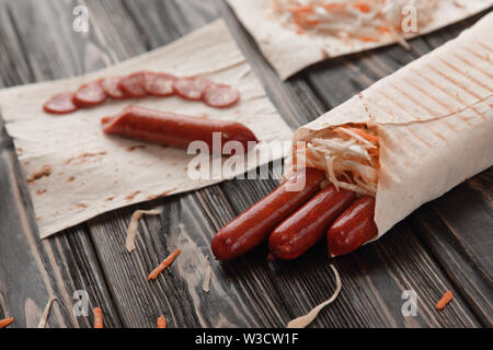 smoked sausage in pita bread on wooden background. - Stock Photo