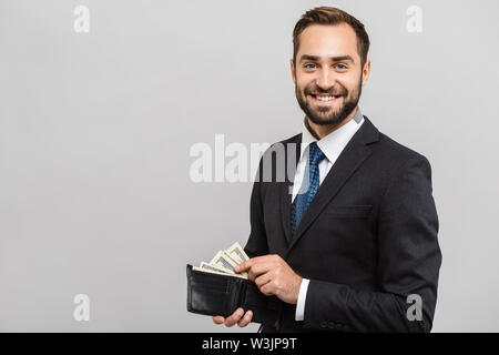 Attractive happy young businessman wearing suit standing isolated over gray background, showing wallet full of money banknotes - Stock Photo