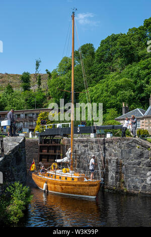 Wooden yacht exiting lock 5 and heading east towards Ardrishaig – Cairnbaan on Crinan Canal, Argyll and Bute, Scotland, UK - Stock Photo