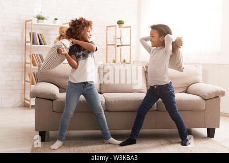 African-american girls having fun, fighting with pillows - Stock Photo