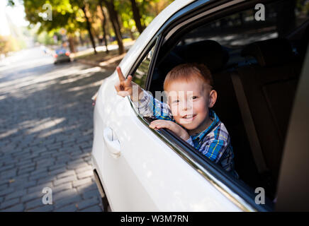 Adorable baby boy in the car. Laughing boy looks out of the car window. - Stock Photo
